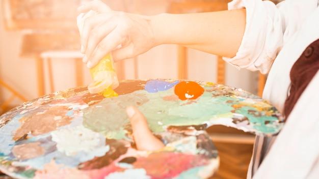 Primo piano della mano che schiaccia il tubo di pittura giallo sulla tavolozza della pittura