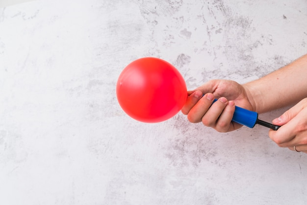 Primo piano della mano che soffia palloncino rosso con pompa contro il muro