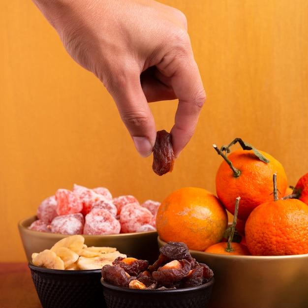 Primo piano della mano che tiene frutta disidratata per il nuovo anno cinese