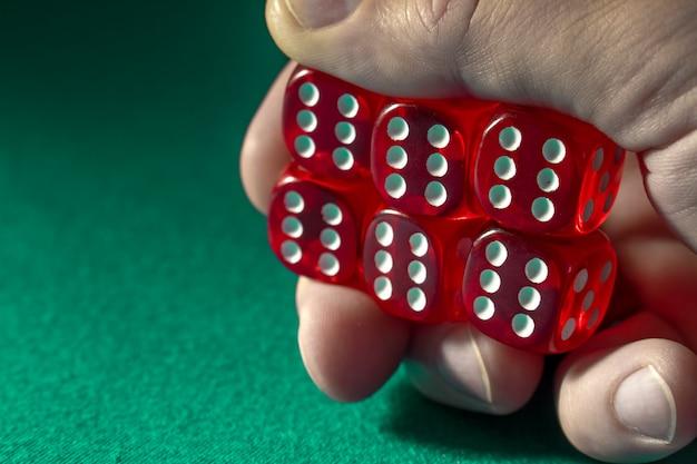Primo piano della mano che tiene i dadi rossi con una combinazione di vincita sul panno verde in un casinò.
