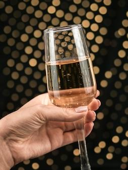 Primo piano della mano che tiene il bicchiere di champagne pieno di bolle