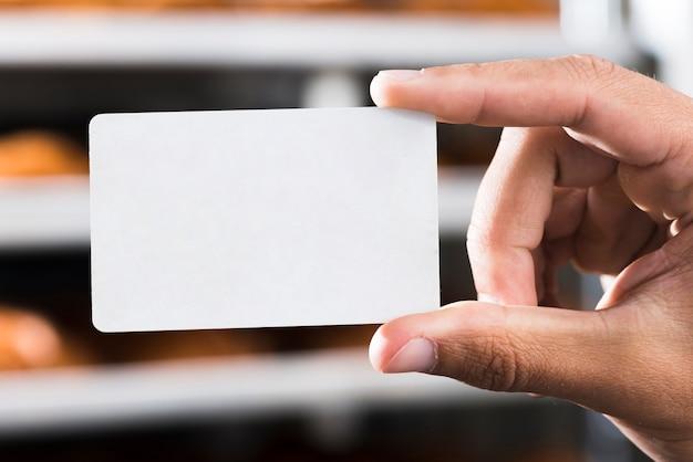 Primo piano della mano che tiene il biglietto da visita rettangolare bianco in bianco