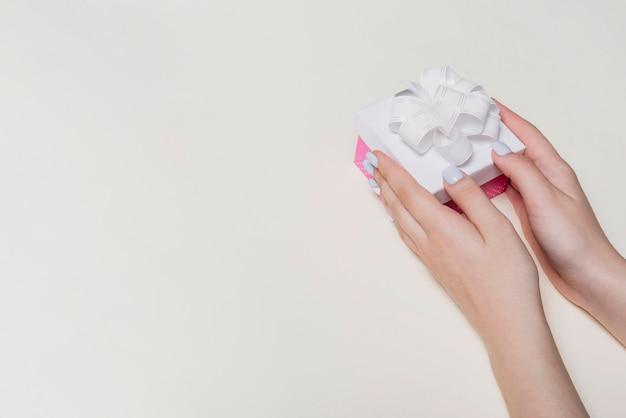 Primo piano della mano che tiene il contenitore di regalo su sfondo bianco
