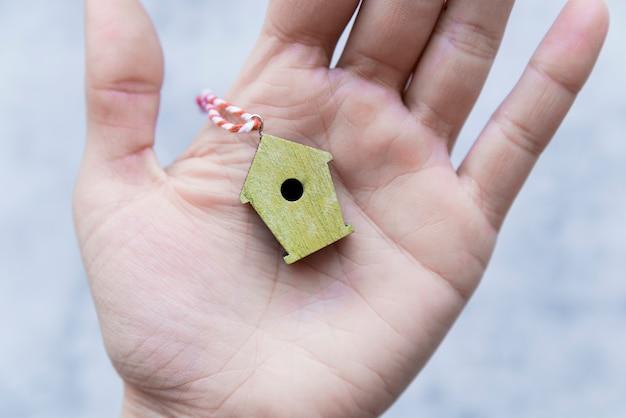Primo piano della mano che tiene l'ornamento di legno giallo dell'aviario