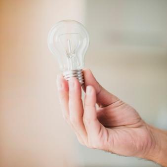 Primo piano della mano che tiene la lampadina su sfocatura sfondo