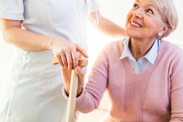Primo piano della mano commovente della persona della donna senior