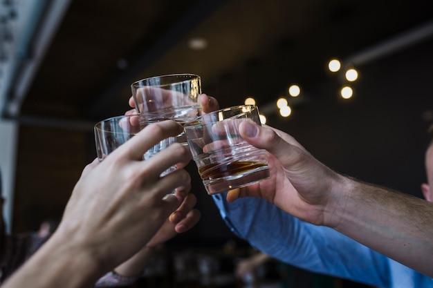 Primo piano della mano degli amici che alza pane tostato con vetro di whiskey