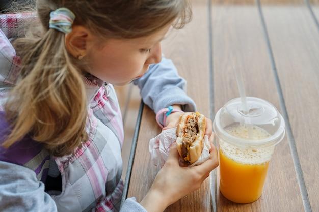 Primo piano della mano del bambino che mangia hamburger e che beve il succo di arancia