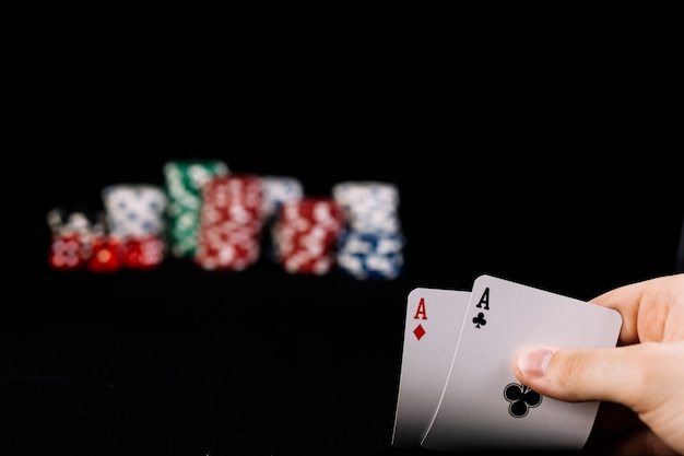 Primo piano della mano del giocatore che tiene due carte da gioco di assi
