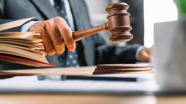 Primo piano della mano del giudice maschile che colpisce il martelletto al tavolo