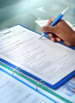 Primo piano della mano del medico femminile con la penna sopra il documento medico