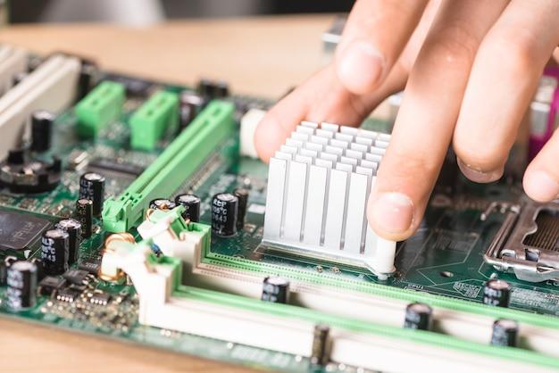Primo piano della mano del tecnico maschio che installa il dissipatore di calore sulla scheda madre del computer