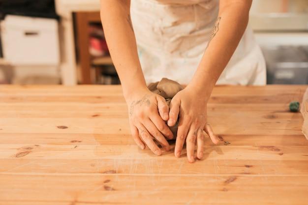 Primo piano della mano del vasaio femminile che impasta l'argilla sulla tavola in officina