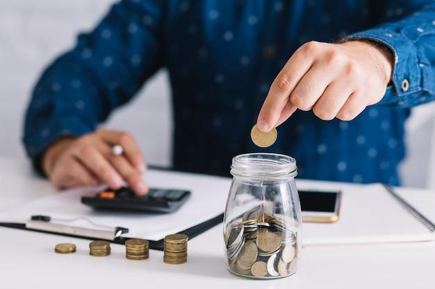 Primo piano della mano dell'uomo che mette moneta in vaso usando la calcolatrice