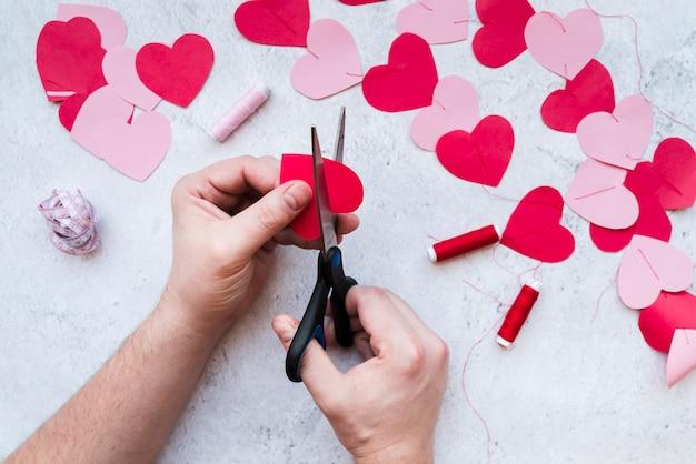 Primo piano della mano dell'uomo che rende la ghirlanda di forma cuore su sfondo bianco strutturato