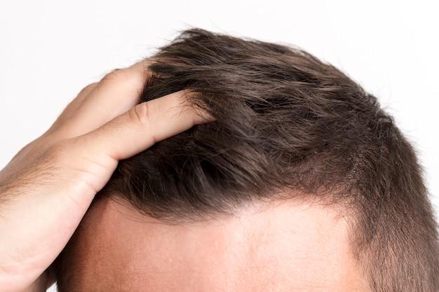 Primo piano della mano dell'uomo che tocca i suoi capelli
