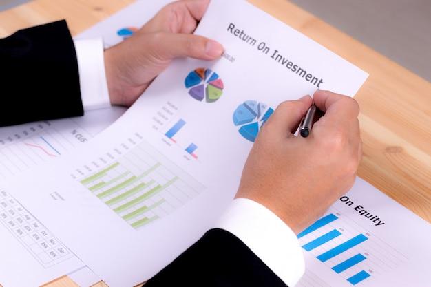 Primo piano della mano dell'uomo d'affari che tiene un documento cartaceo del rapporto finanziario di ritorno sull'investimento