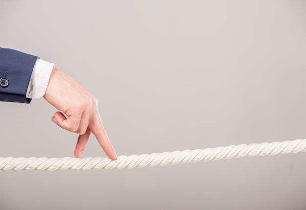 Primo piano della mano dell'uomo di affari che cammina con le dita sulla corda.