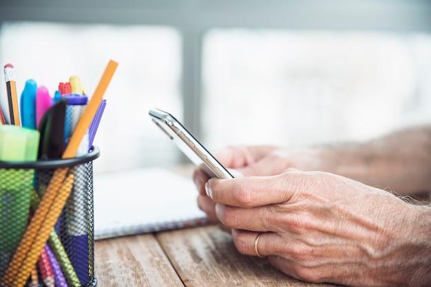 Primo piano della mano dell'uomo senior che tiene smart phone
