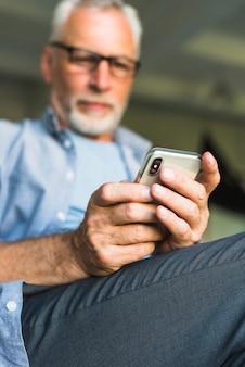 Primo piano della mano dell'uomo senior che tiene telefono mobile