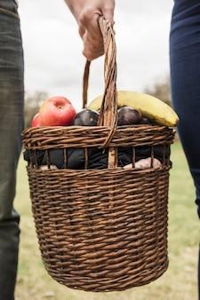 Primo piano della mano della coppia che tiene il cestino di picnic pieno di frutta