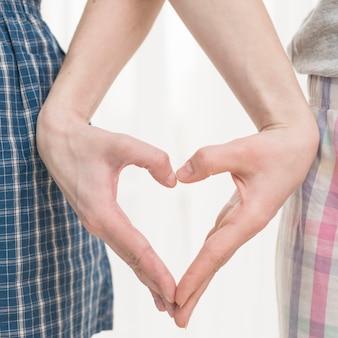 Primo piano della mano della coppia lesbica che fa figura del cuore