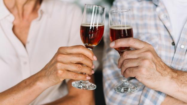 Primo piano della mano della coppia senior che tosta i vetri di vino
