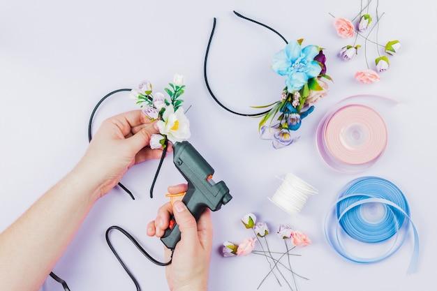 Primo piano della mano della donna che attacca i fiori sul fermaglio per capelli con la pistola di colla calda elettrica sul contesto bianco