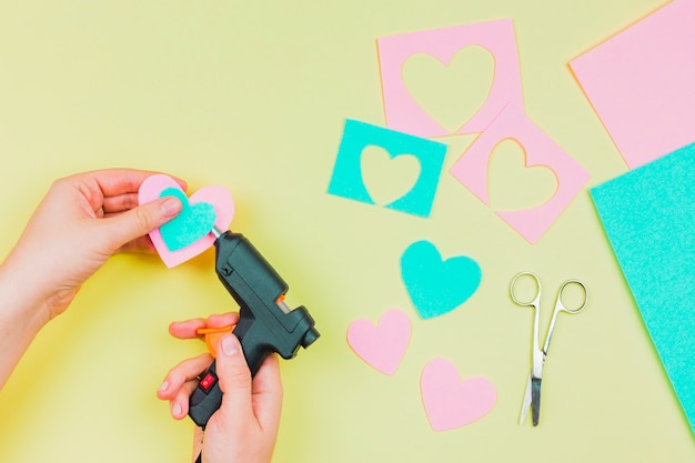 Primo piano della mano della donna che attacca la forma di cuore di carta con la pistola per colla a caldo elettrica