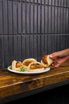 Primo piano della mano della donna che cattura il bao del gua sul piatto bianco sopra la tavola di legno