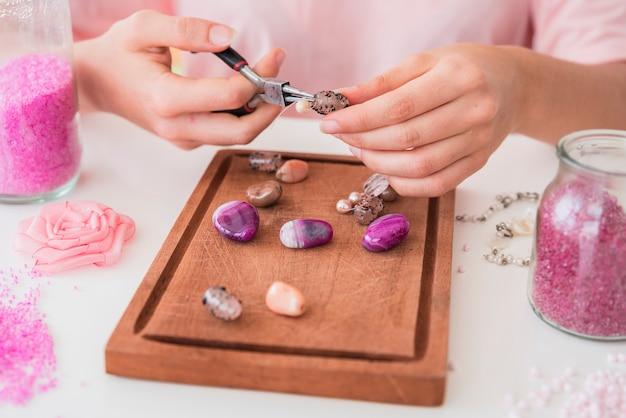 Primo piano della mano della donna che fa il braccialetto di perline sul vassoio in legno