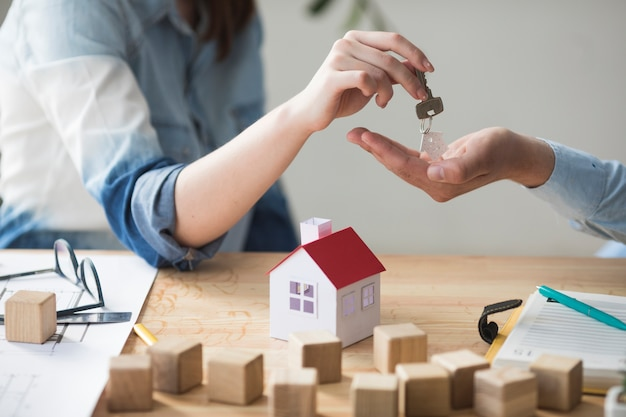 Primo piano della mano della donna che fornisce la chiave della casa all'uomo sopra il tavolo in legno