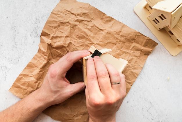 Primo piano della mano della donna che liscia il modello di casa in legno sopra la carta marrone stropicciata