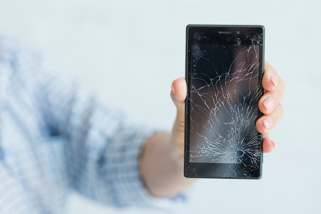 Primo piano della mano della donna che mostra schermo mobile rotto