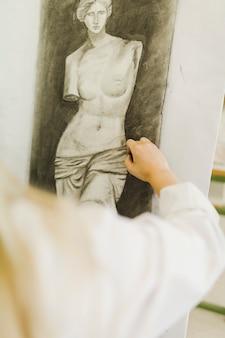 Primo piano della mano della donna che schizza scultura su tela