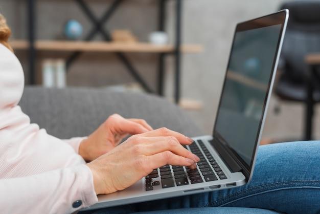 Primo piano della mano della donna che scrive sul computer portatile