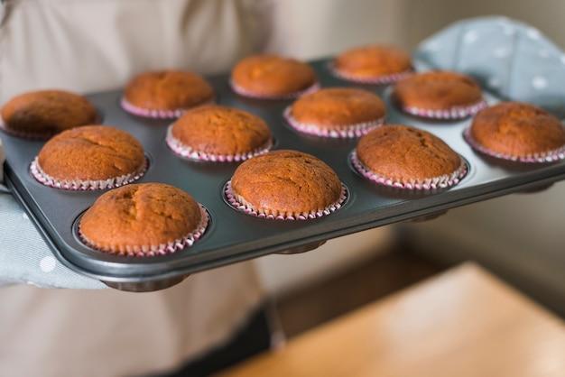Primo piano della mano della donna che tiene i muffin al forno nel vassoio di cottura