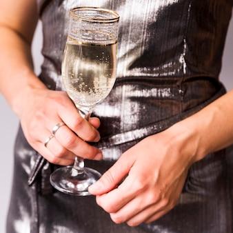 Primo piano della mano della donna che tiene il bicchiere di champagne rinfrescante