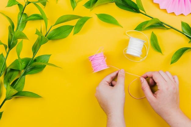 Primo piano della mano della donna che tiene la bobina rosa del filo con le foglie verdi sul contesto giallo