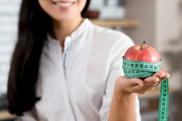 Primo piano della mano della donna che tiene mela rossa con nastro di misurazione verde
