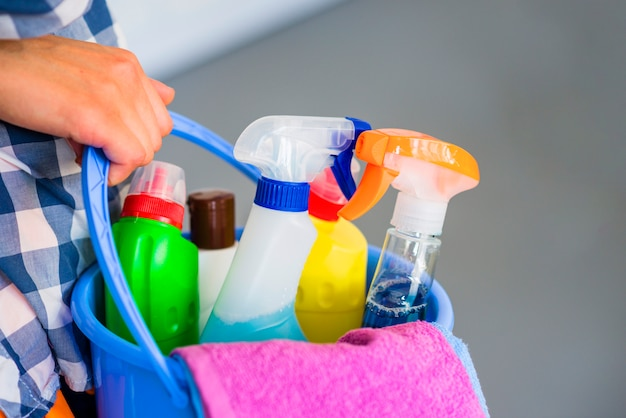 Primo piano della mano della donna che tiene secchio blu con attrezzature per la pulizia