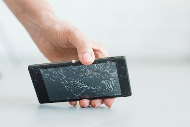 Primo piano della mano della donna che tiene smartphone con schermo rotto