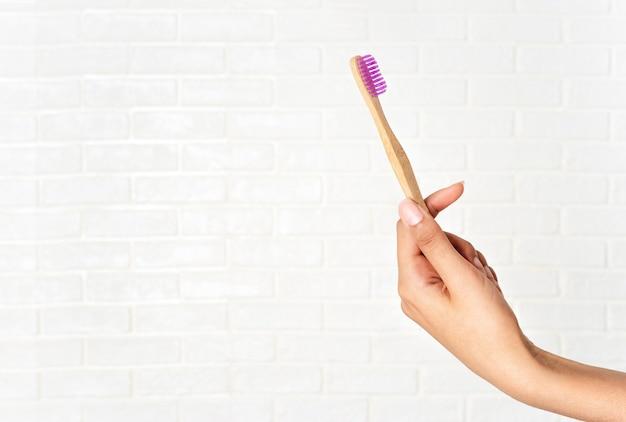 Primo piano della mano della donna che tiene spazzolino da denti di bambù