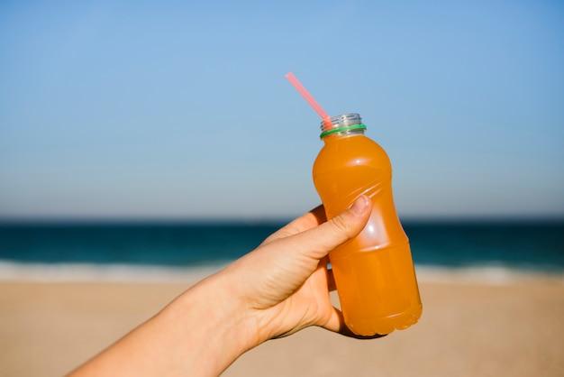 Primo piano della mano della donna che tiene una bottiglia di plastica del succo d'arancia con cannuccia alla spiaggia