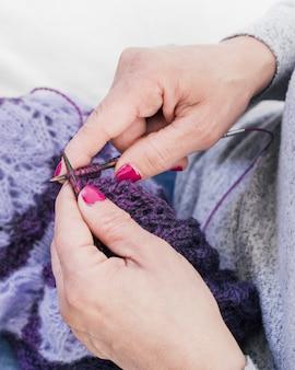 Primo piano della mano della donna che tricotta lana viola