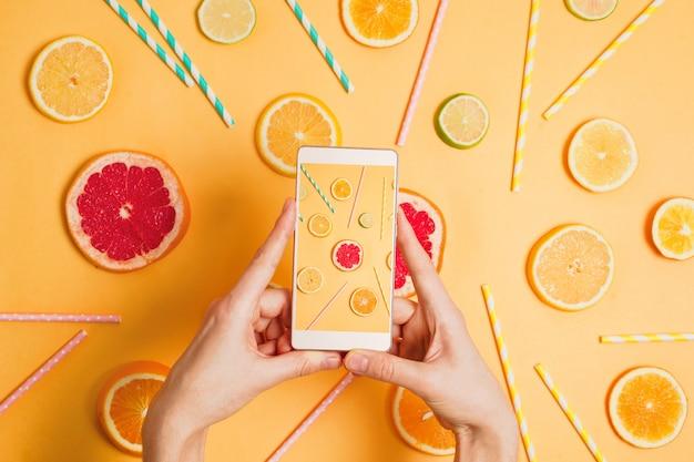 Primo piano della mano della donna con uno smartphone che fa immagine di varia disposizione del flatlay degli agrumi. messa a fuoco selettiva. fotografia di cibo o concetto di blog.
