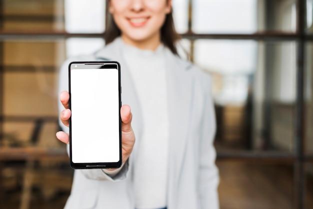 Primo piano della mano della donna di affari che mostra il cellulare dello schermo in bianco all'ufficio