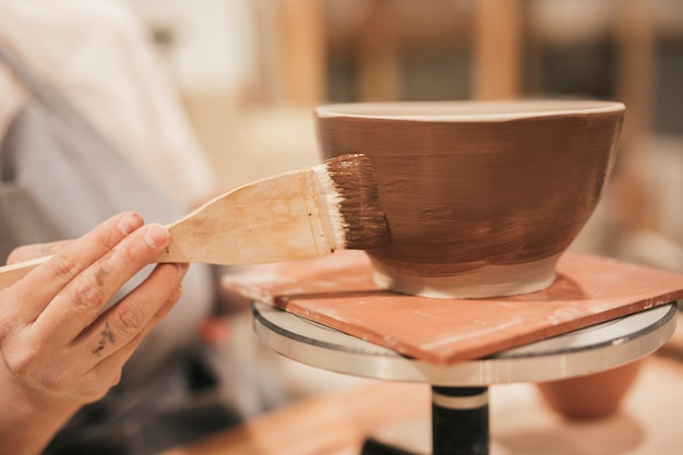 Primo piano della mano della femmina che applica la pittura marrone sulla ciotola con il pennello