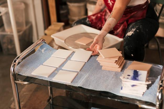Primo piano della mano della femmina che asciuga le mattonelle bianche