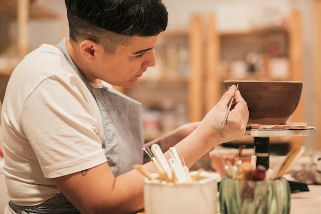 Primo piano della mano della femmina che dipinge sulla ciotola di ceramica con gli strumenti